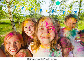 Happy kids' faces smeared with colored powder