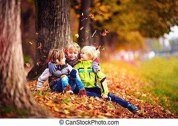 happy kids, friend having fun among fallen leaves in autumn park