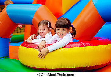 happy kids, girls having fun on inflatable attraction ...
