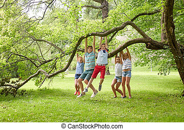 happy kids hanging on tree in summer park - friendship, ...