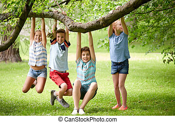 happy kids hanging on tree in summer park - friendship,...
