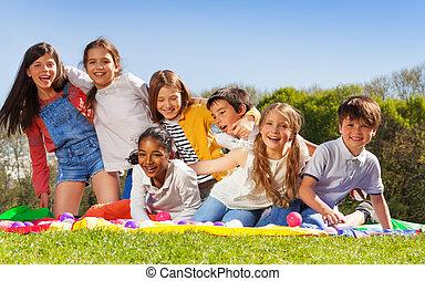 Happy kids having fun sitting on the lawn in park