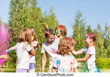 Happy kids having fun with colored powder outside