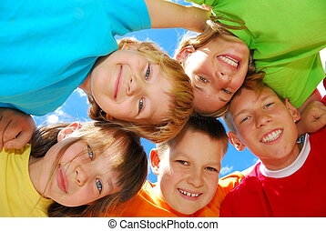 Five smiling kids, huddled together...shot from inside the huddle, with the blue sky in the background
