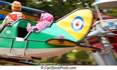 Happy kids in autumn amusement park ride - happy kids in...