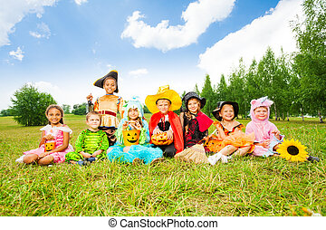Happy kids in Halloween costumes sit on grass