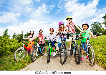 Happy kids in row wear colorful bike helmets holding bike handle-bars and are ready to ride their bikes in summer