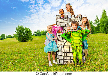 Happy kids in theatric costumes play around tower
