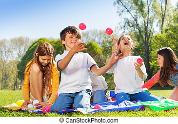 Happy kids juggling with little balls in the park