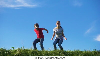 Happy kids jumping on green grass hill against blue sky