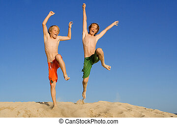 happy kids jumping on summer beach vacation