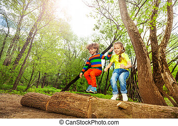 Happy kids jumping over a log in the summer forest
