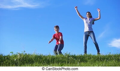 Happy kids jumping together on green grass hill against blue sky