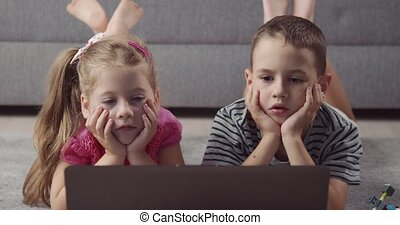 Happy kids lying on carpet and watching cartoons on laptop