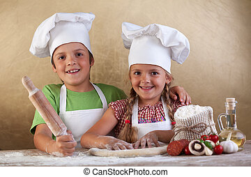 Happy kids making pizza togheter - Happy kids with chef hats...