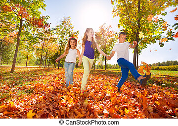 Happy kids play with autumn leaves in the forest