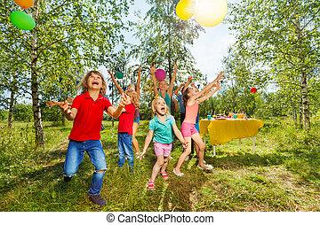Happy kids playing balloons at summer park