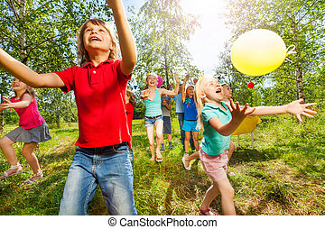 Happy kids playing balloons outdoor in summer