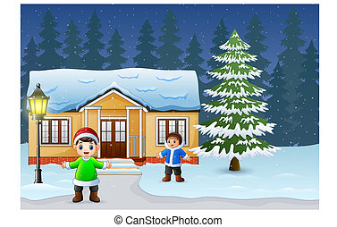 Happy kids playing in front of the snowing house