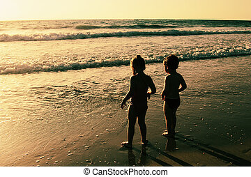 happy kids playing on the beach at