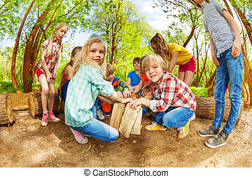 Happy kids playing with wooden logs in the forest