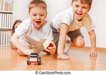 Happy kids playing with wooden toy car at floor