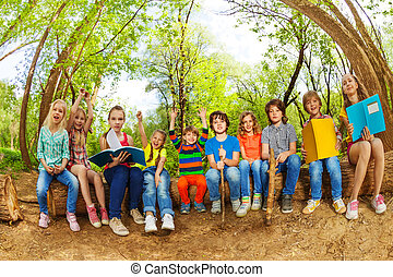 Happy kids reading books outdoor in summer camp - Big group...