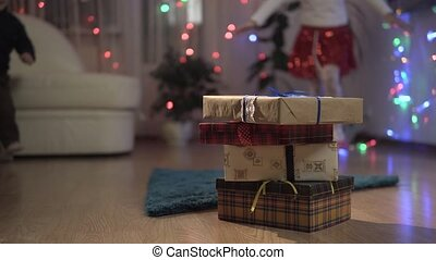 Happy kids runs to their Christmas gift surprise boxes