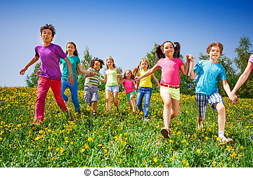 Happy kids run and hold hands in green meadow during summer