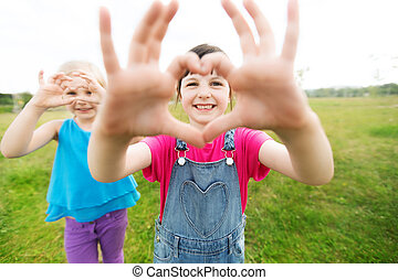 happy kids showing heart shape sign outdoors - summer,...