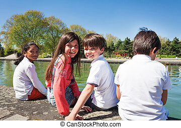 Four happy kids sitting on the embankment and looking out to water