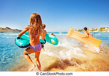 Happy kids splashing water while running into sea
