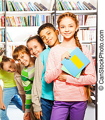 Happy kids standing in row inside library