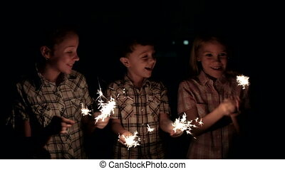 Happy kids standing on the road and burning sparkles at the night time.