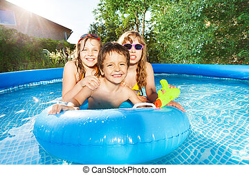 Happy kids swimming in the pool with rubber ring