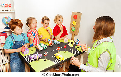 Happy kids teaching traffic signs in kindergarten - Four...