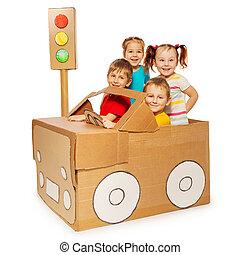 Happy kids travelling by cardboard car