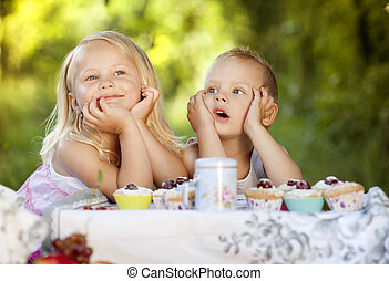Happy kids - Two happy kids having picnic outside in summer