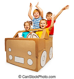 Happy kids waving hands sitting in cardboard car