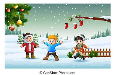 Happy kids wearing a winter chlotes playing on the snow in christmas day