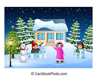 Happy kids wearing a winter clotes playing a snow in the christmas day