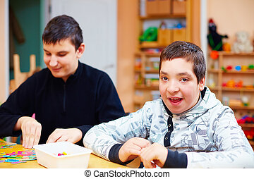 happy kids with disability develop their fine motor skills...