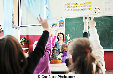 happy kids with teacher in school classroom - happy young...