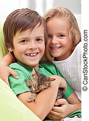 Happy kids with their new pet - a little kitten