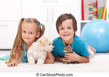 Happy kids with their pets - a dog and a kitten, laying on...
