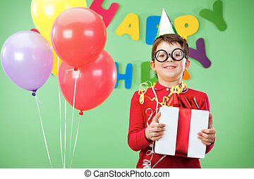 Portrait of happy lad in funny eyeglasses on birthday party with giftbox