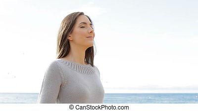 Happy lady breathing fresh air on the beach