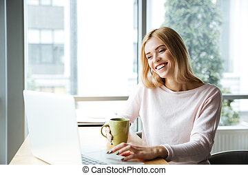 Happy lady sitting in office coworking while using laptop computer