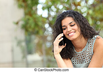 Happy lady talking on phone sitting in a park