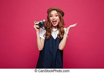 Happy lady wearing like parisian holding retro camera and loking camera